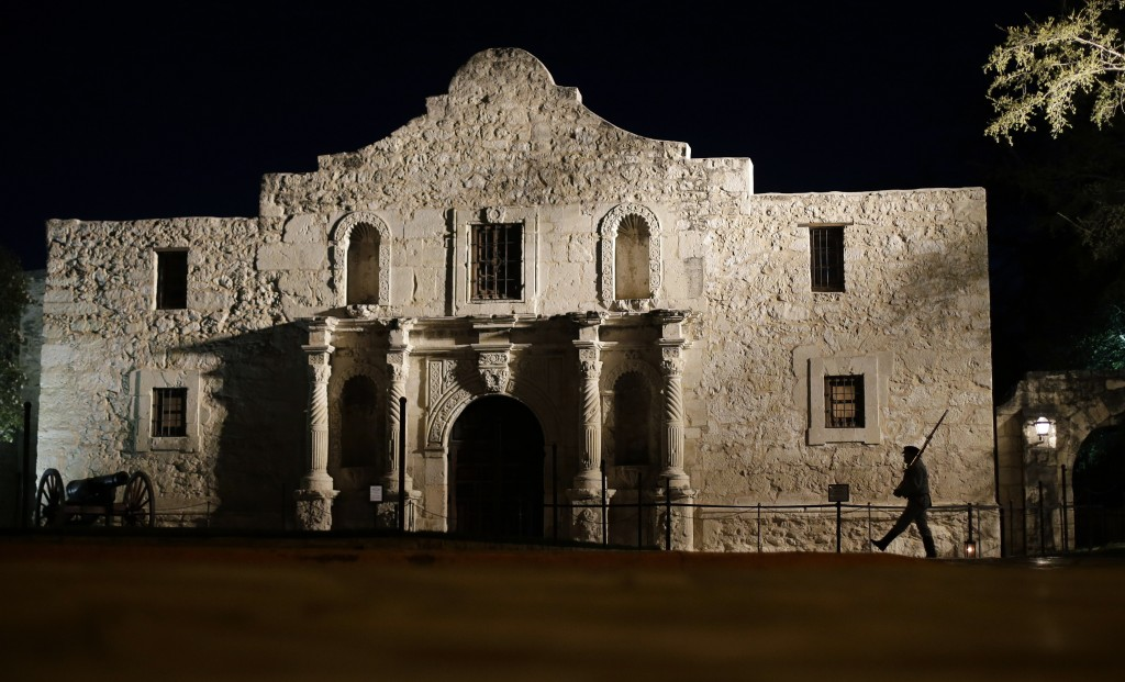 FILE - In this March 6, 2013, file photo, John Potter, a member of the San Antonio Living History Association, patrols the Alamo in San Antonio, durin...