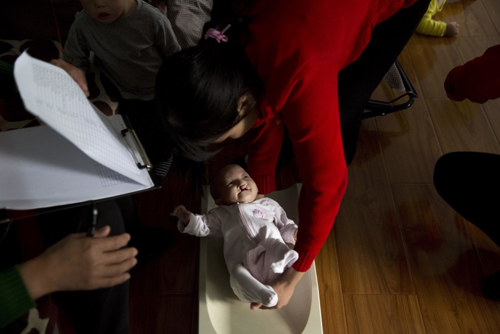 A minder lifts a child with cleft lip from a scale at a foster home of the New Hope Foundation on the outskirts of Beijing, China, on Wednesday, Oct. ...