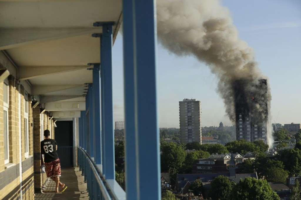 FILE - In this Wednesday, June 14, 2017 file photo a resident in a nearby high-rise building watches smoke rise from a massive fire at the high-rise G...