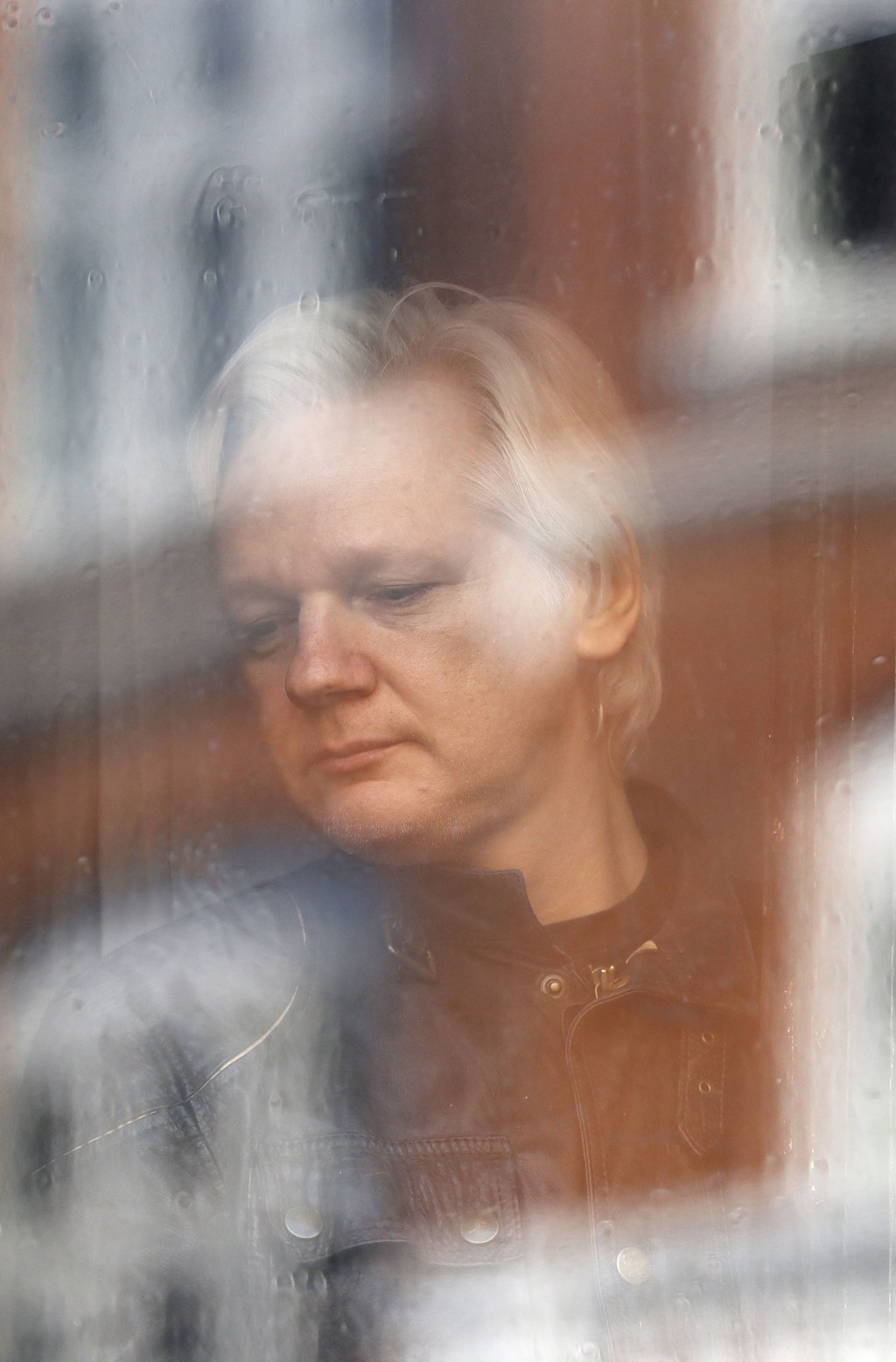 FILE - In this Friday May 19, 2017 file photo Julian Assange looks out the window from the Ecuadorian embassy in London. Sweden's top prosecutor says ...
