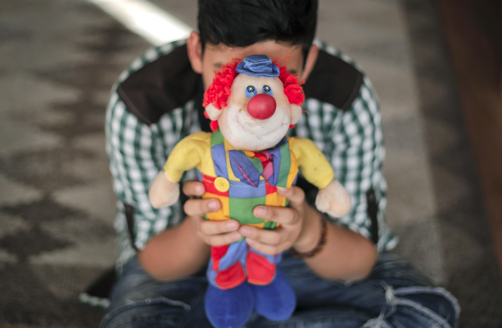 A boy living in a family-style home for abandoned children poses for a photo covering his face with a clown doll in Bucharest, Romania, on Wednesday, ...