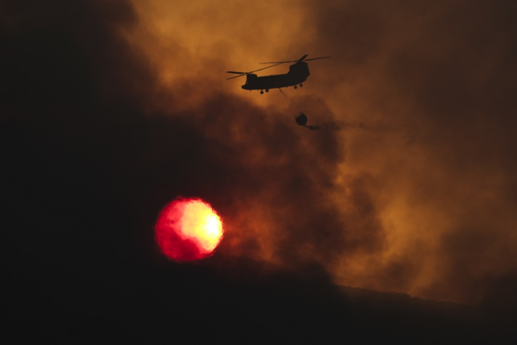 FILE - In this Tuesday Aug. 15, 2017 file photo a fire fighting helicopter flies amid smoke as the sun sets during a forest fire near Kapandriti north...