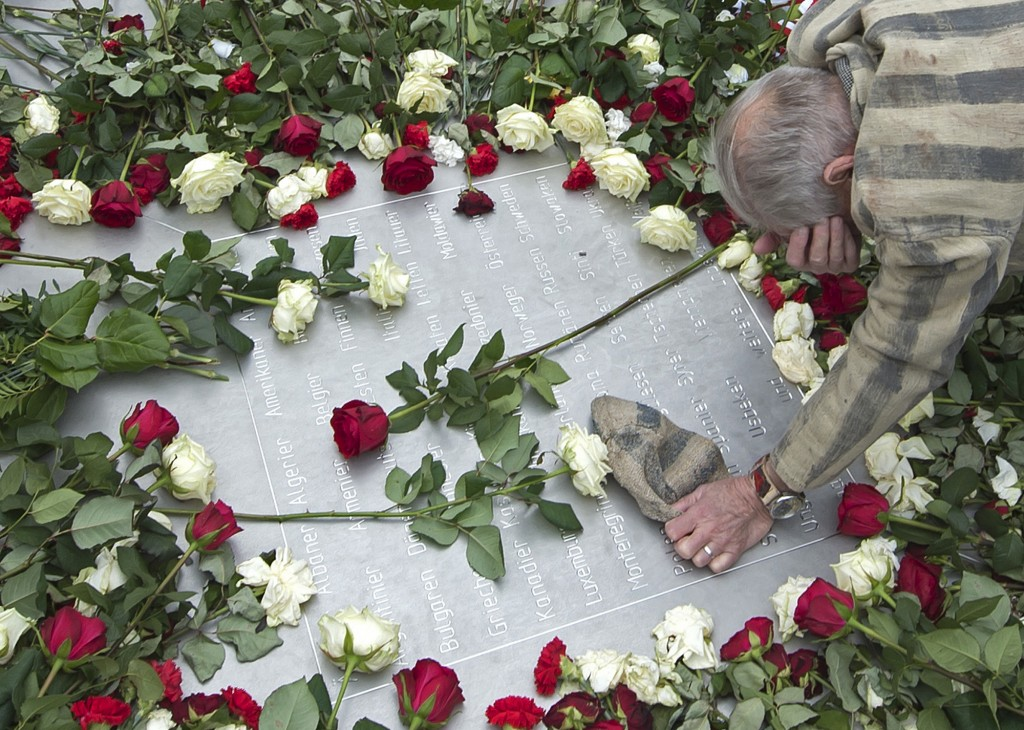 FILE - In this Tuesday, April 11, 2017 file photo Nazi concentration camp survivor Alexander Bytschok of Kiev, Ukraine, mourns on a metal plaque durin...