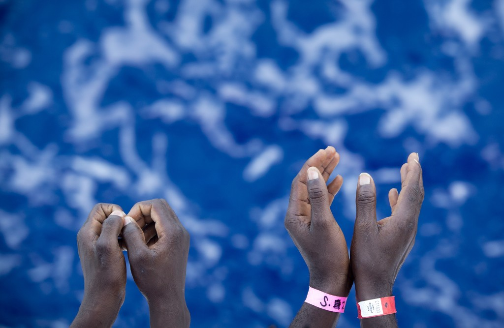 FILE - In this Thursday, Aug. 31, 2017 file photo African migrants gesture as stand on the deck of the Aquarius vessel of SOS Mediterranee and MSF (Do...