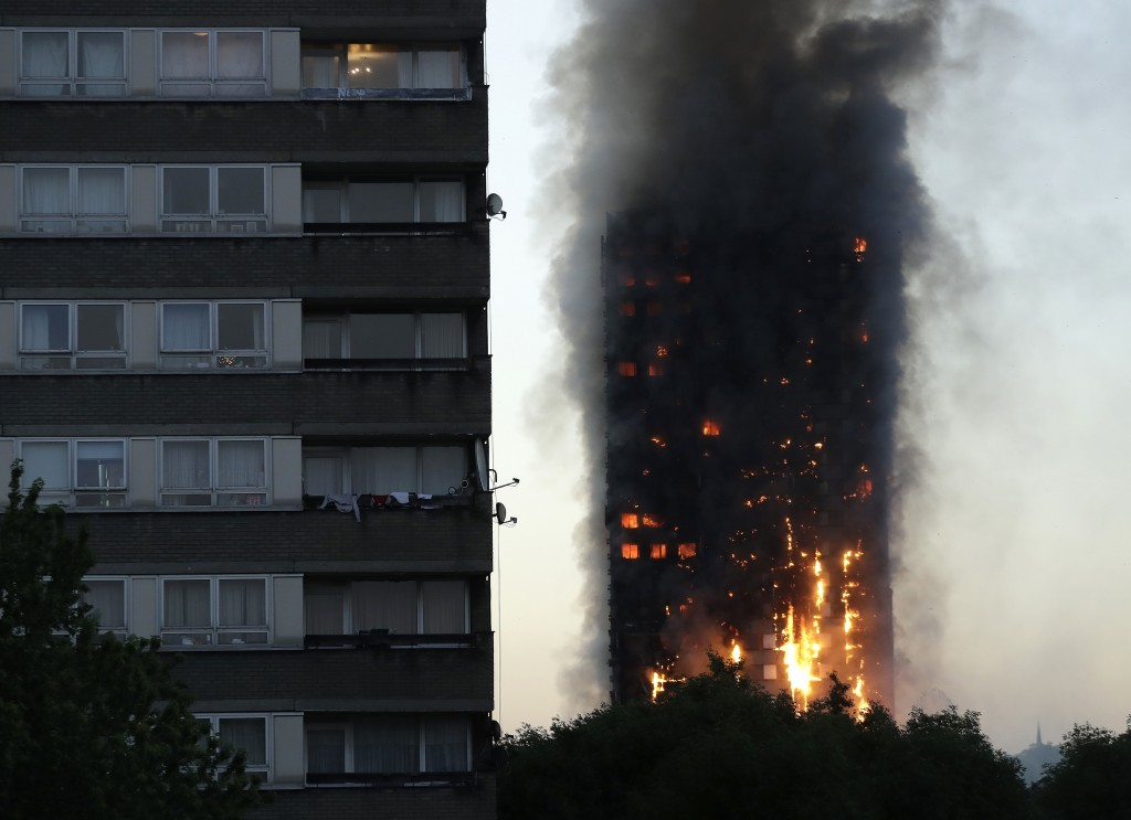 FILE - In this Wednesday, June 14, 2017 file photo smoke and flames rise from the Grenfell Tower high-rise building in west London. (AP Photo/Matt Dun...