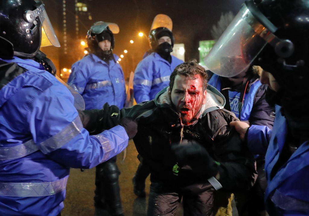 FILE - In this Thursday, Feb. 2, 2017 file photo Romanian riot police detain a man, face covered in blood, after minor clashes erupted during a protes...