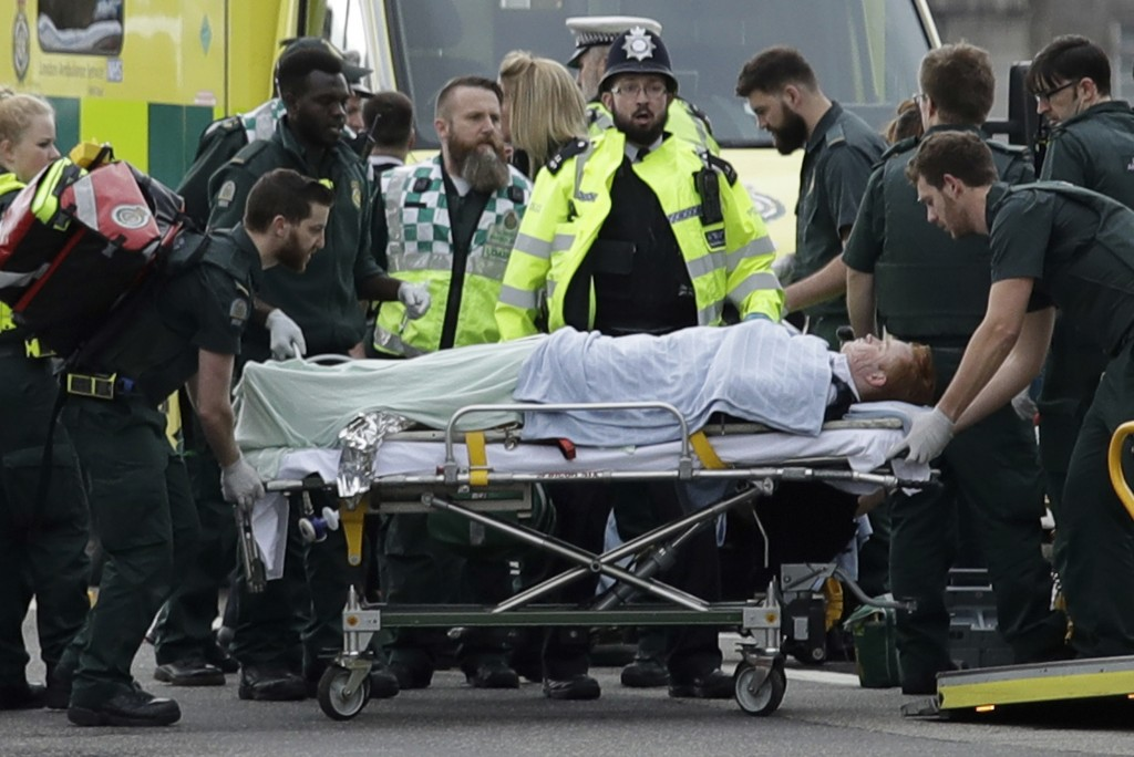 FILE - In this Wednesday, March 22, 2017 file photo emergency services staff provide medical attention to injured people on Westminster Bridge, near t...