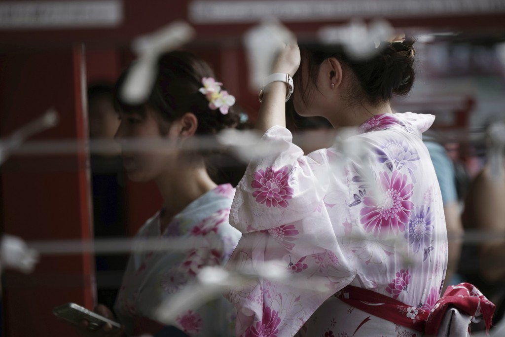 """FILE - In this Aug. 22, 2017, file photo, visitors wearing a traditional Japanese summer kimono or """"yukata"""" stroll through a temple in Tokyo. U.S. vis..."""