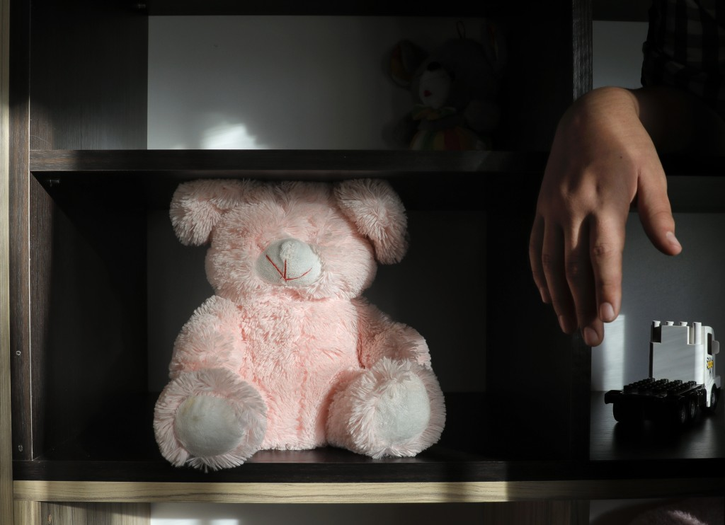 A boy stands next to a teddy bear missing its eyes at a foster home in Bucharest, Romania, on Wednesday, Nov. 1, 2017. Once infamous for its orphanage...