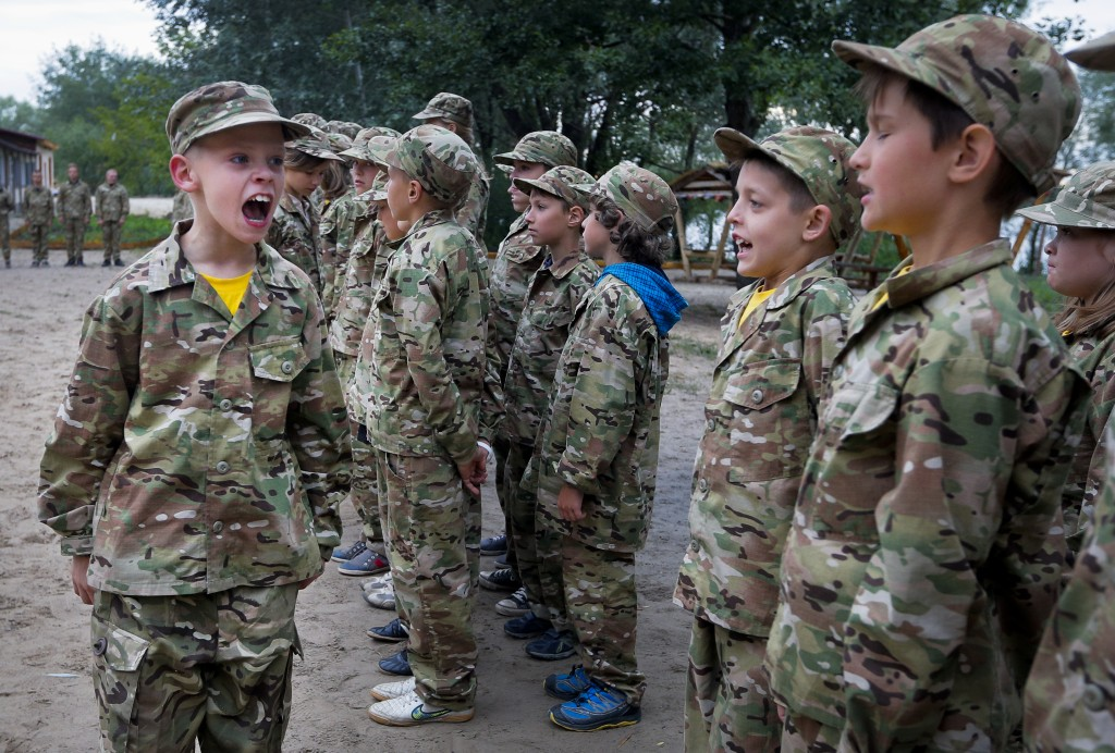 In this photo taken on Friday, July 14, 2017, a student at a paramilitary camp for children calls the rank to attention outside Kiev, Ukraine. As the ...