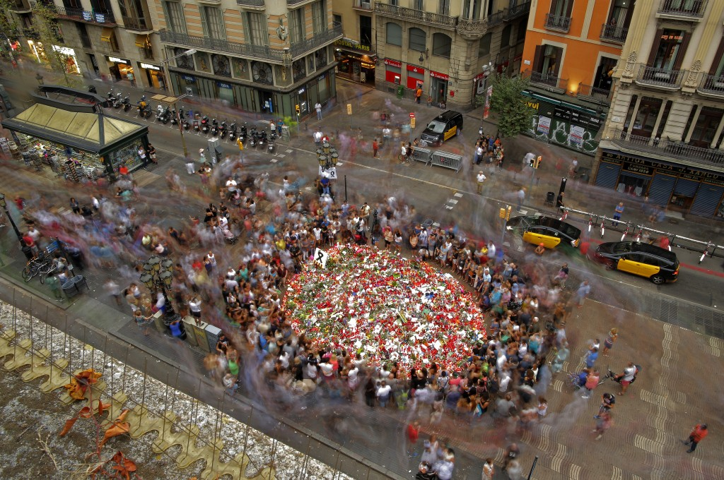 FILE - In this Saturday, Aug. 19, 2017 file photo people pay respect at a memorial tribute of flowers, messages and candles to the victims on Barcelon...