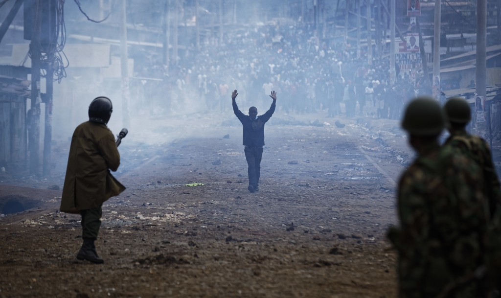 FILE - In this Thursday, Aug. 10, 2017 file photo a man seeking safety walks with his hands in the air through a thick cloud of tear gas towards riot ...