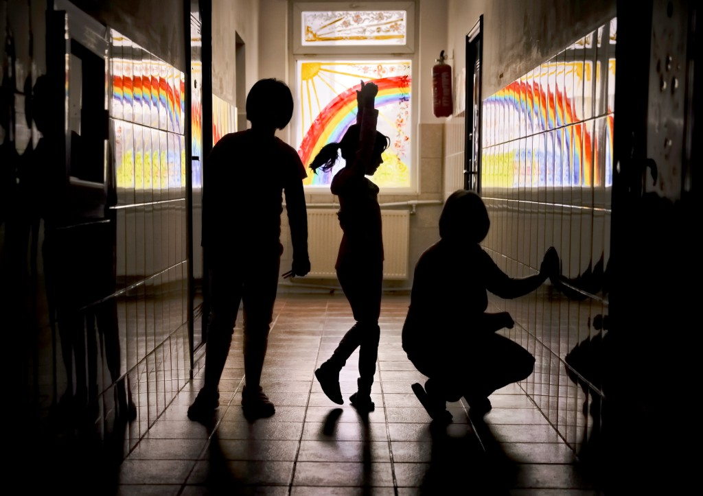 Sara, a child living at the Robin Hood orphanage, tries a ballet move while posing for a photo with other children in a corridor with painted windows,...