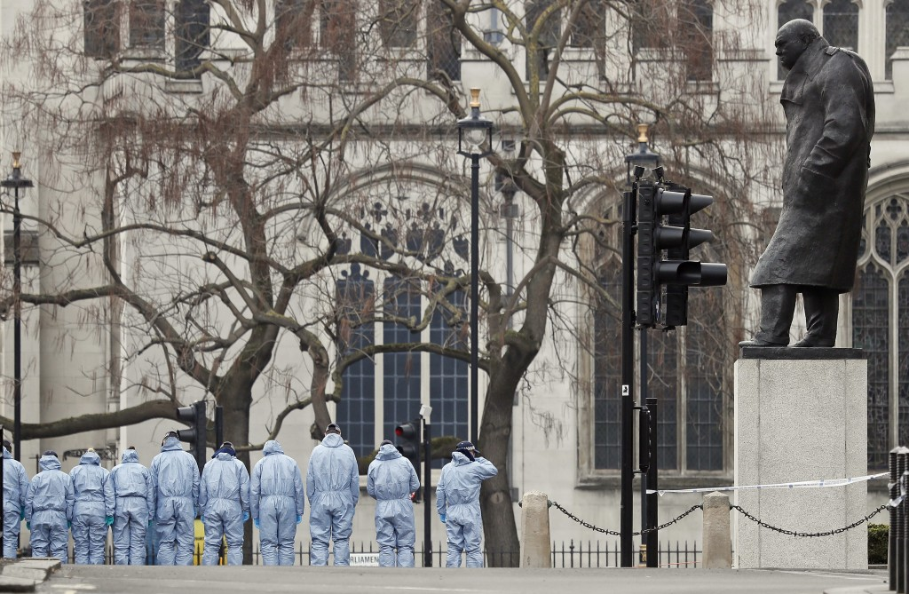 FILE - In this Thursday March 23, 2017 file photo police forensic officers work in Parliament Square overseen by the statue of Winston Churchill outsi...
