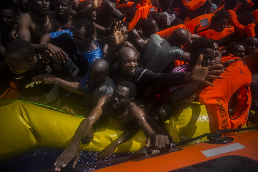 FILE - In this Tuesday, July 25, 2017 file photo sub-Saharan migrants receive life jackets as they are rescued by aid workers of Spanish NGO Proactiva...