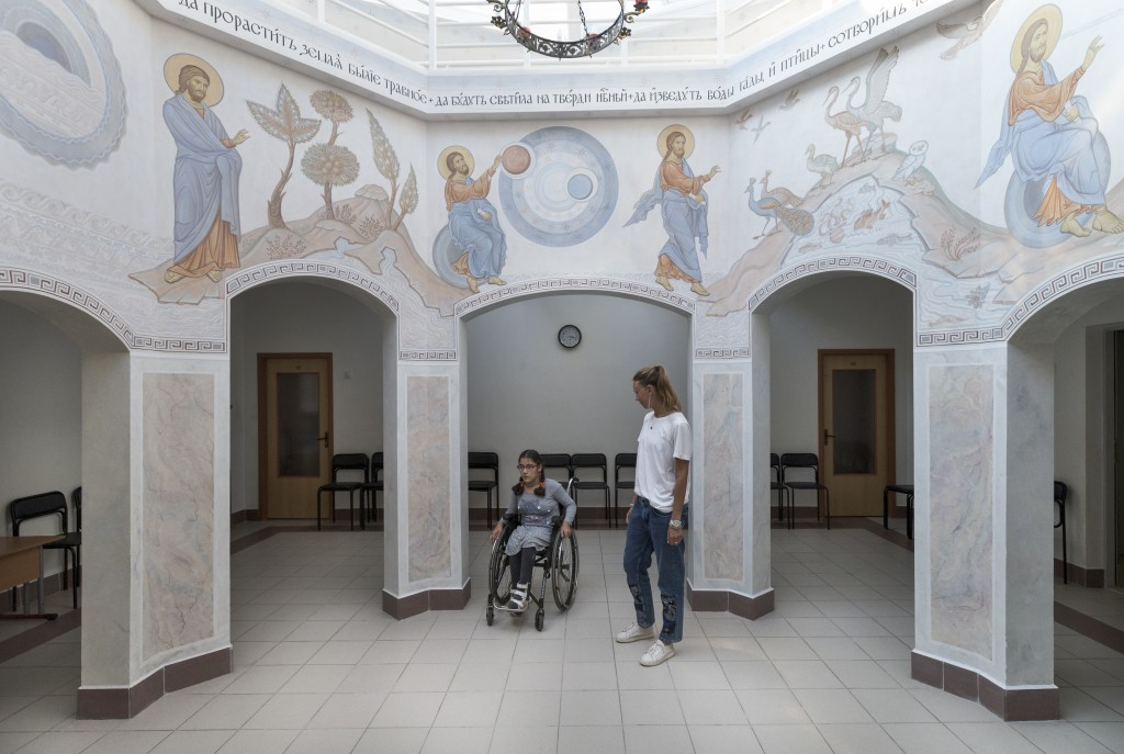 Tutor Valeria and 11-year-old pupil Feruza cross through a chapel at the St. Sophia orphanage in Moscow, Russia, on Tuesday, Sept. 12, 2017. According...