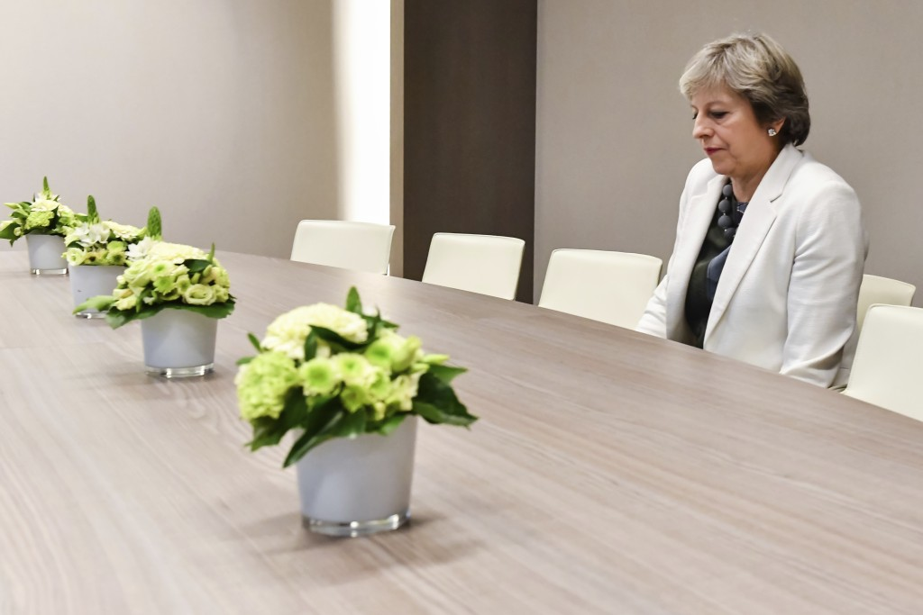 FILE - In this Friday, Oct. 20, 2017 file photo British Prime Minister Theresa May waits for the arrival of European Council President Donald Tusk pri...
