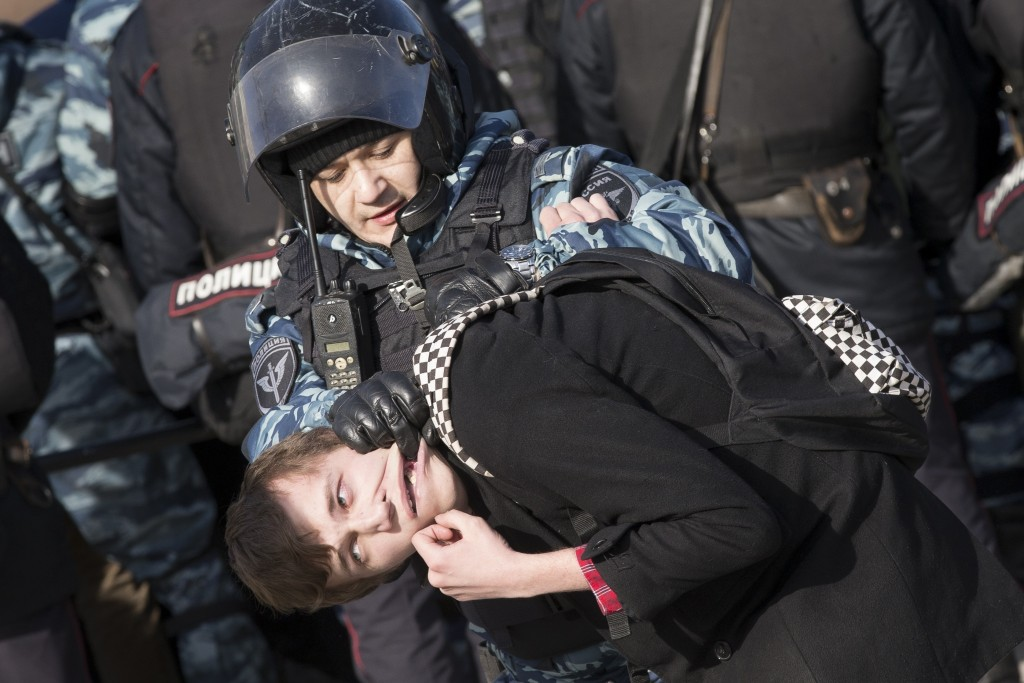 FILE - In this Sunday, March 26, 2017 file photo police detain a protester in downtown Moscow, Russia. Thousands of people crowded into Moscow's Pushk...