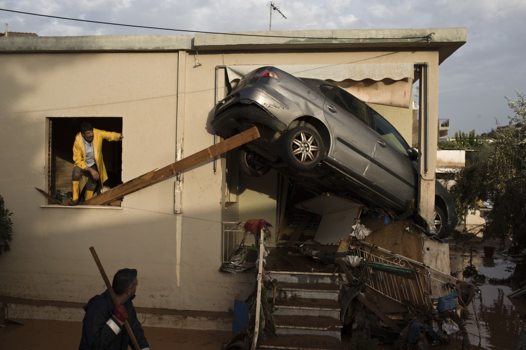 FILE - In this Thursday, Nov. 16, 2017 file photo, workers try to remove a vehicle wedged into the entrance of a home in the town of Mandra western At...