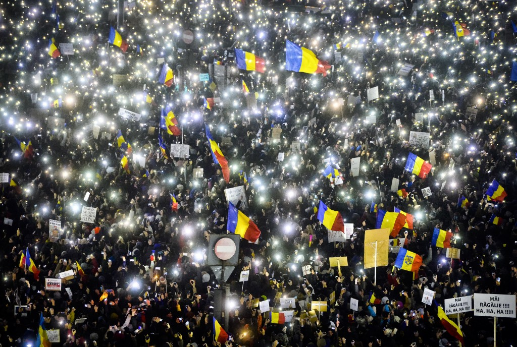 FILE - In this Sunday, Feb. 5, 2017 file photo tens of thousands of people shine lights from mobile phones and torches during a protest in front of th...