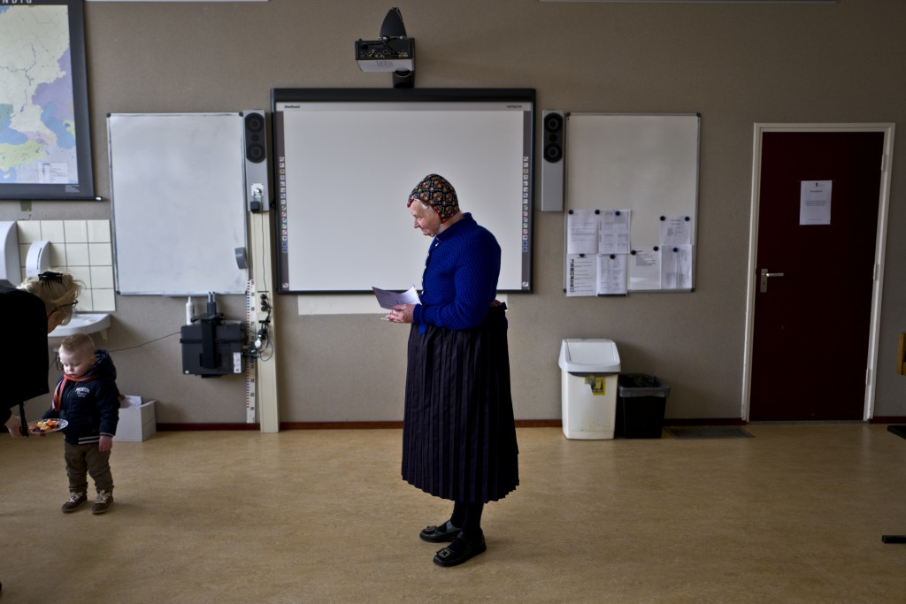 FILE - In this Wednesday, March 15, 2017 file photo an elderly woman wearing a traditional hat waits her turn to cast her vote for the Dutch general e...