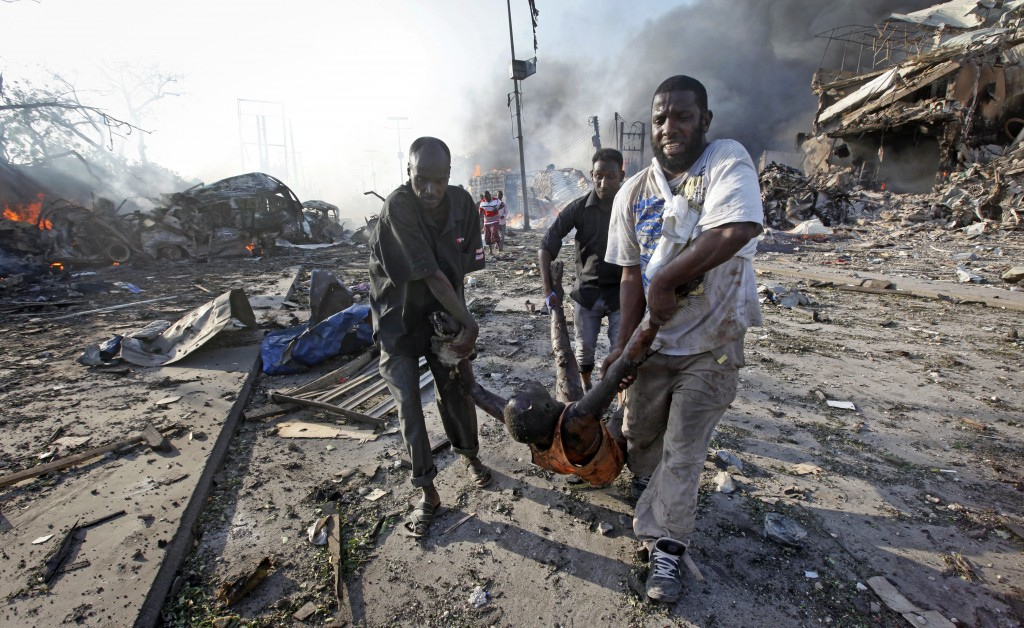 FILE - In this Saturday, Oct. 14, 2017 file photo Somalis remove the body of a man killed in a blast in the capital Mogadishu, Somalia. A huge explosi...