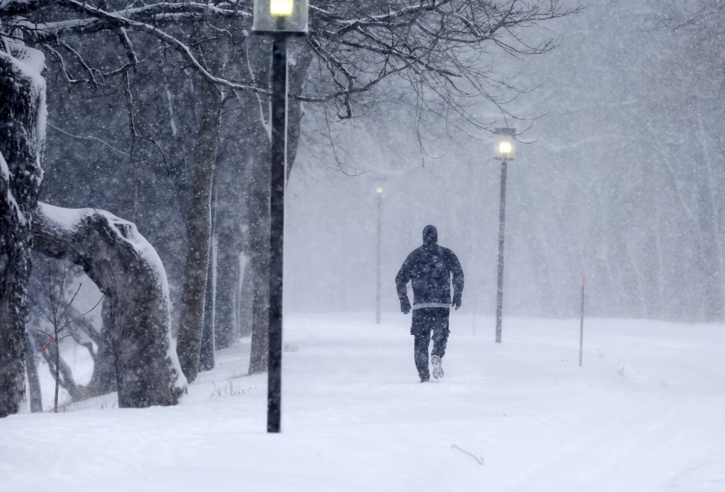 FILE - In this Feb. 2, 2016, file photo, street lights are illuminated as a jogger runs around Lake Harriet in a Minneapolis heavy snow storm. Thousan...