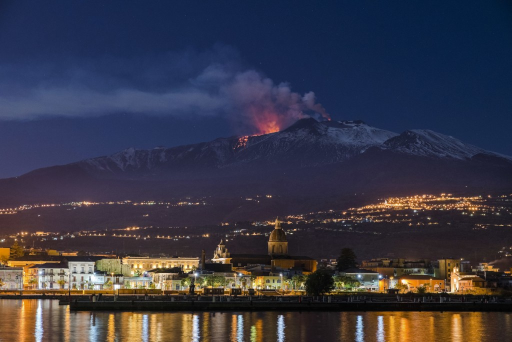 FILE - In this Tuesday, April 11, 2017 file photo Mount Etna, Europe's most active volcano, spews lava as the Sicilian town of Riposto, Italy, is visi...