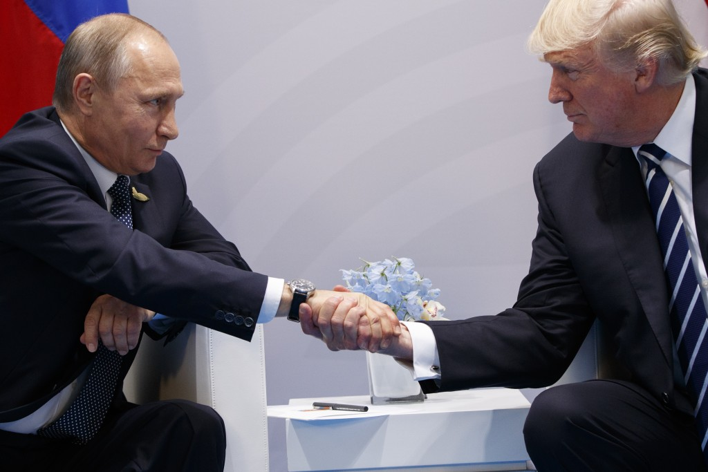 FILE - In this Friday, July 7, 2017 file photo President Donald Trump shakes hands with Russian President Vladimir Putin at the G20 Summit in Hamburg....