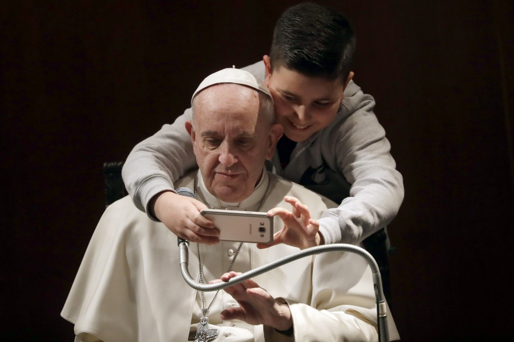 FILE - In this Sunday, Feb. 19, 2017 file photo a boy takes a selfie with Pope Francis, during a visit to the parish of Santa Maria Josefa del Cuore d...