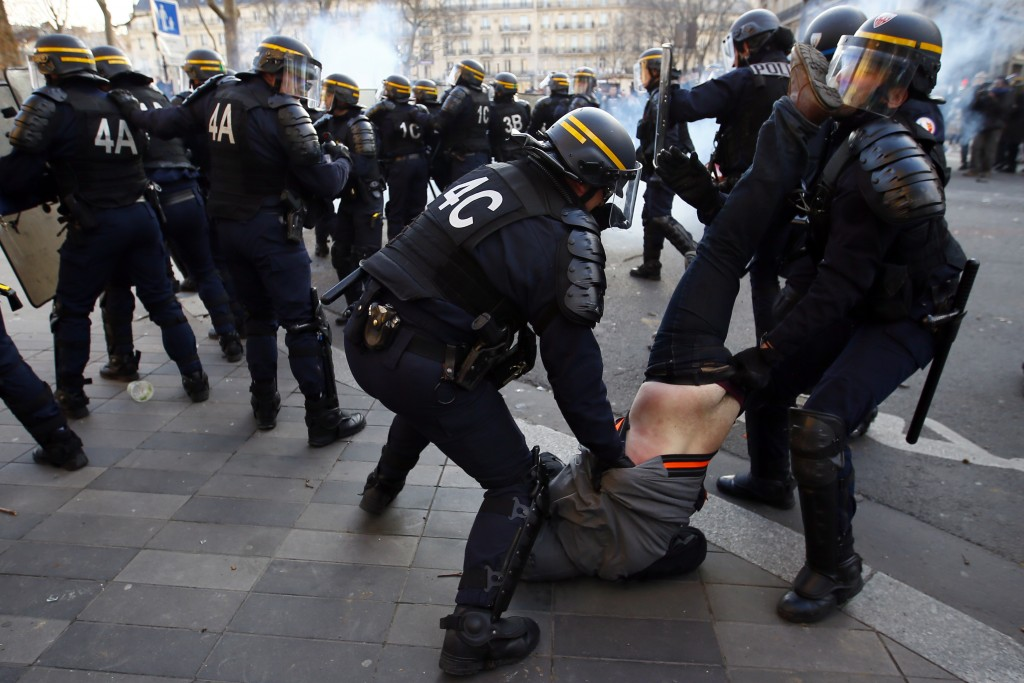 FILE - In this Saturday, Feb. 18, 2017 file photo riot Police officers apprehend a protester during clashes at a demonstration against alleged police ...