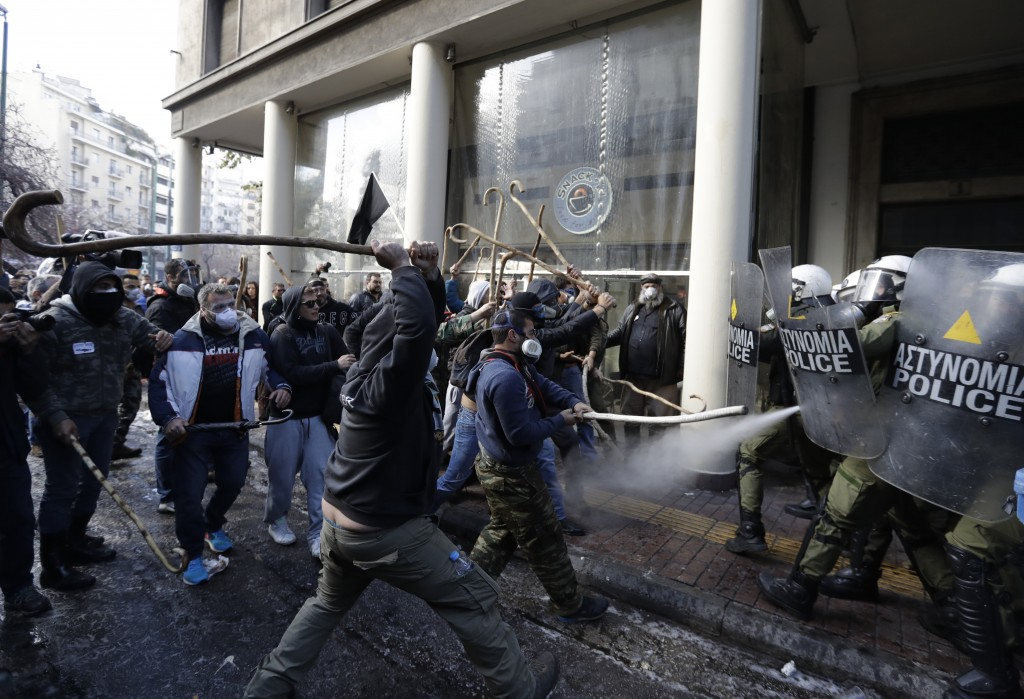 FILE - In this Wednesday, March 8, 2017 file photo riot police clash with protesting farmers outside the greek Agriculture Ministry, in Athens. Police...