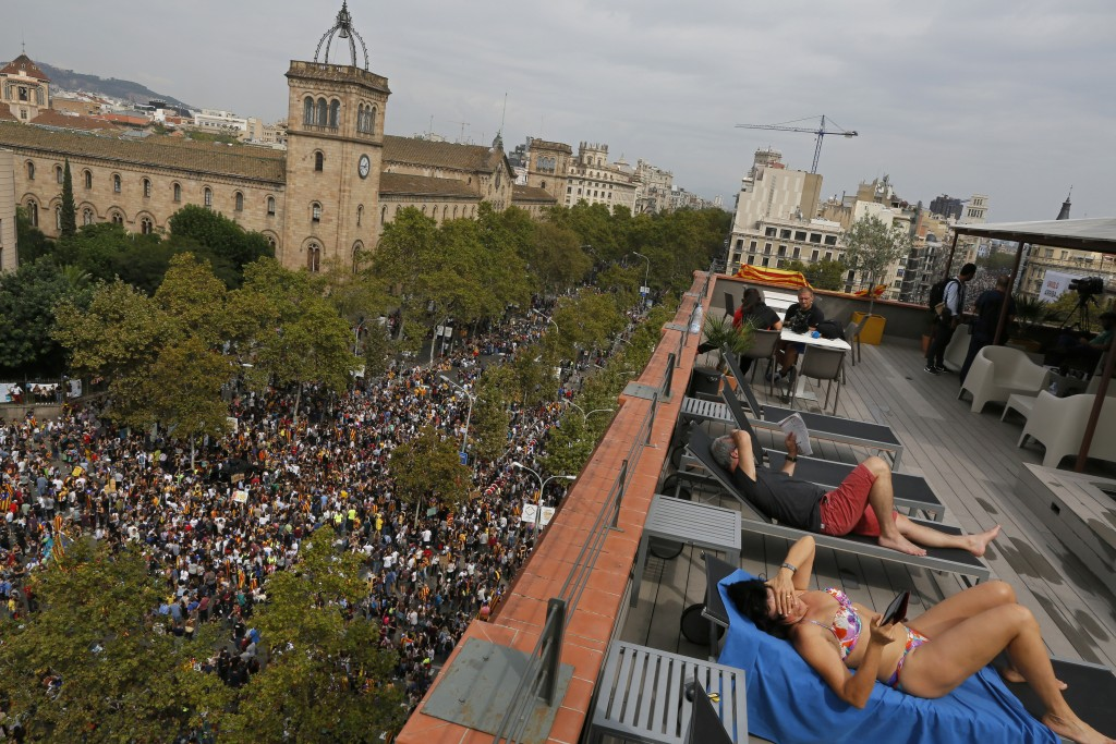 FILE - In this Tuesday Oct. 3, 2017 file photo a couple, tourists from Switzerland, sunbath at a terrace overlooking Universitat square as demonstrato...