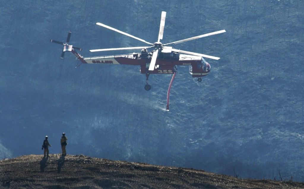 In this photo provided by the Santa Barbara County Fire Department, a Skycrane helicopter passes firefighters atop a hillside while coming in for a wa...