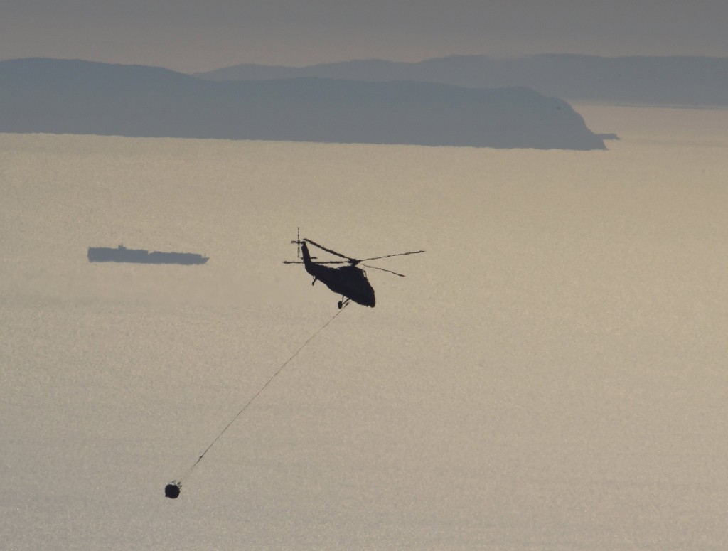In this photo provided by the Santa Barbara County Fire Department, a pilot takes his firefighting helicopter back to fill its bucket with water while