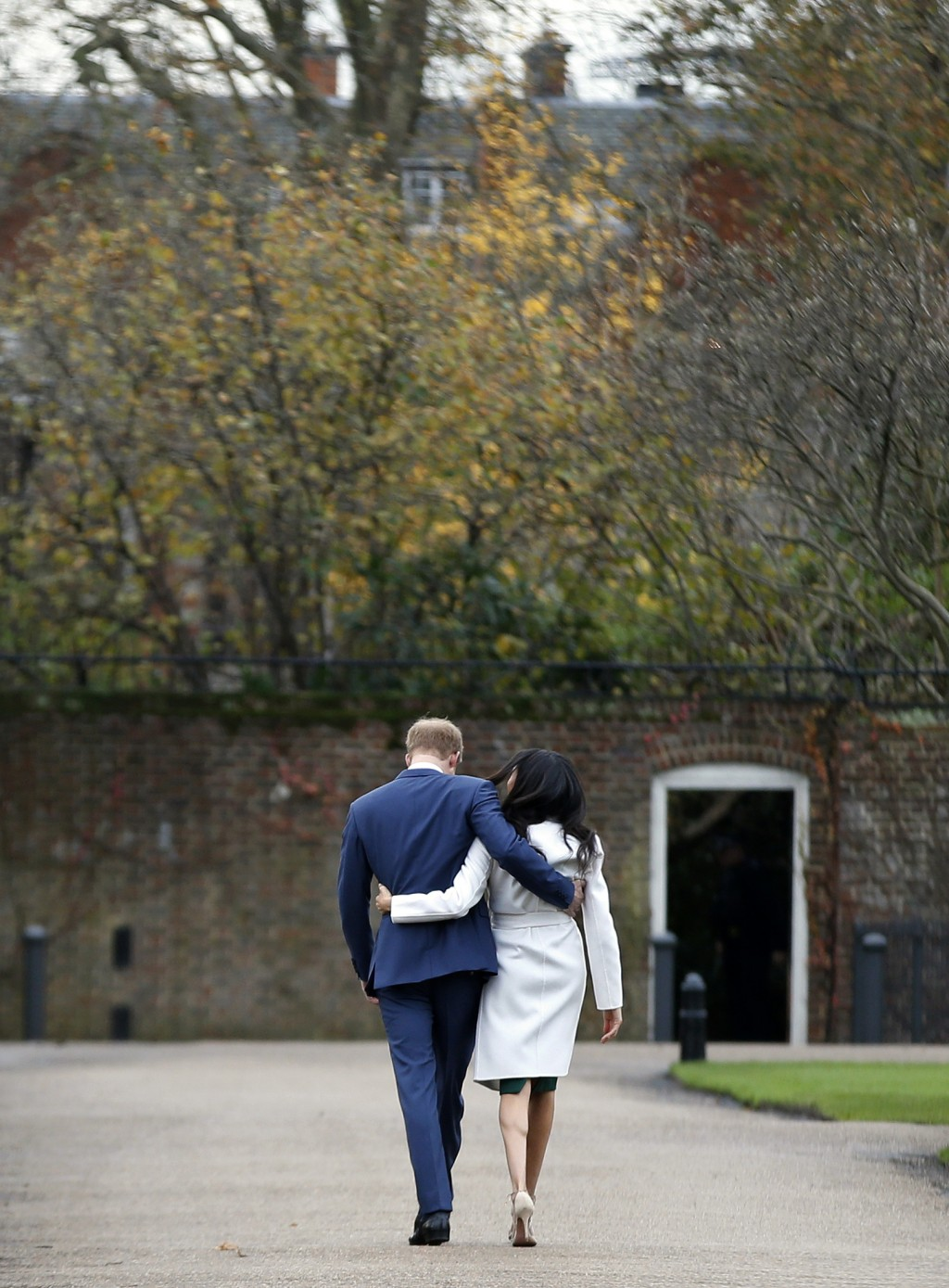 FILE - In this Monday Nov. 27, 2017 file photo Britain's Prince Harry and Meghan Markle walk away after posing for the media in the grounds of Kensing...