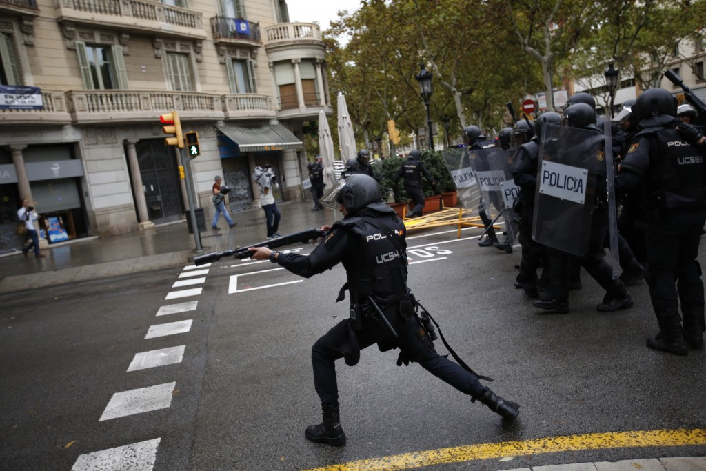 FILE - In this Sunday, 1 Oct. 2017 file photo Spanish riot police shoots rubber bullet straight to people trying to reach a voting site at a school as...
