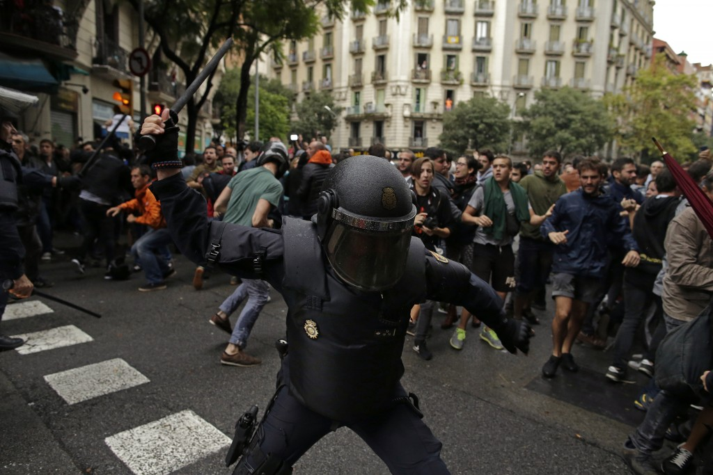FILE - In this Sunday, 1 Oct. 2017 file photo Spanish riot police swings a club against would-be voters near a school assigned to be a polling station...