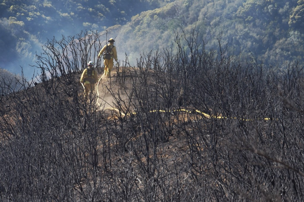 In this photo provided by the Santa Barbara County Fire Department, firefighters follow a hose line while walking rugged and scorched terrain below E.