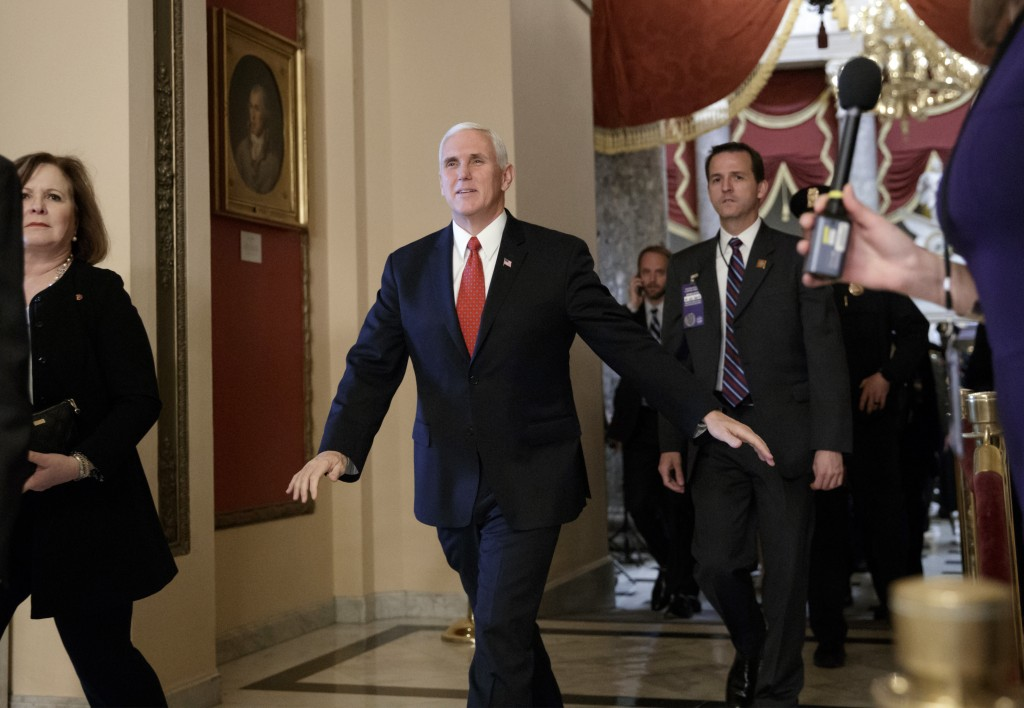 Vice President Mike Pence strides through the Capitol to the House Chamber to watch the passage of the Republican tax bill, in Washington, Tuesday, De