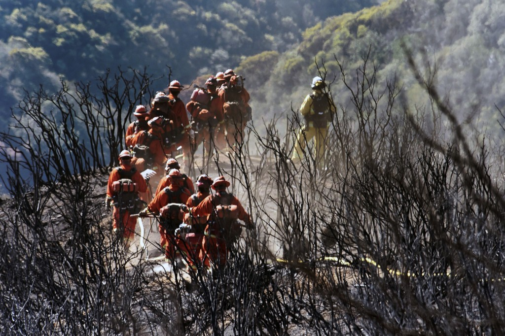 In this photo provided by the Santa Barbara County Fire Department, CAL FIRE Inmate Firefighting Hand Crew members hike through the charred landscape ...