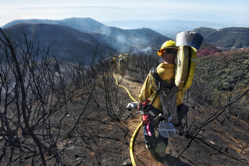 In this photo provided by the Santa Barbara County Fire Department, Santa Barbara County Firefighters haul dozens of pounds of hose and equipment down
