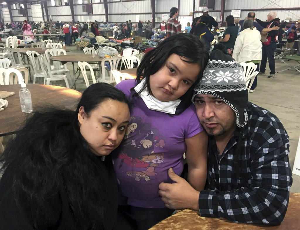 FILE - In this Dec. 6, 2017, file photo wildfire survivors, Marolyn Romero-Sim, left, with Hugo Romero-Rodriguez, center, and their 9-year-old daughte...