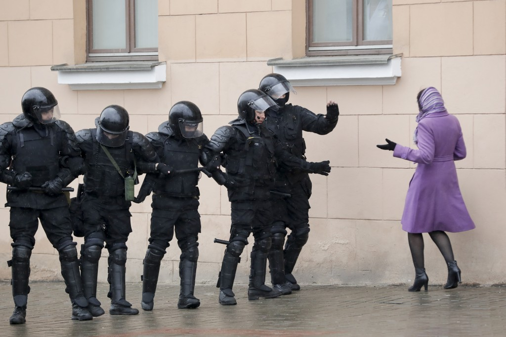 FILE - In this Saturday, March 25, 2017 file photo a woman argues as Belarus police block a street during an opposition rally in Minsk, Belarus. A cor...