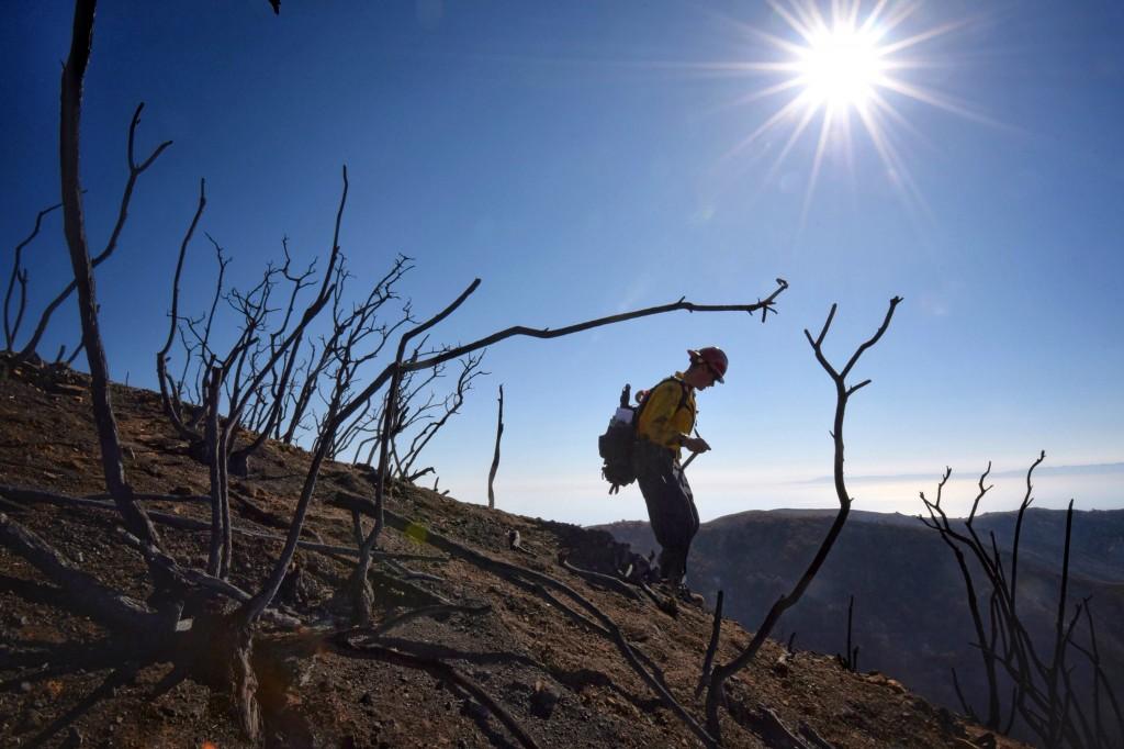 In this photo provided by the Santa Barbara County Fire Department, Santa Barbara County Fire Capt. Ryan Thomas hikes down steep terrain below East Ca