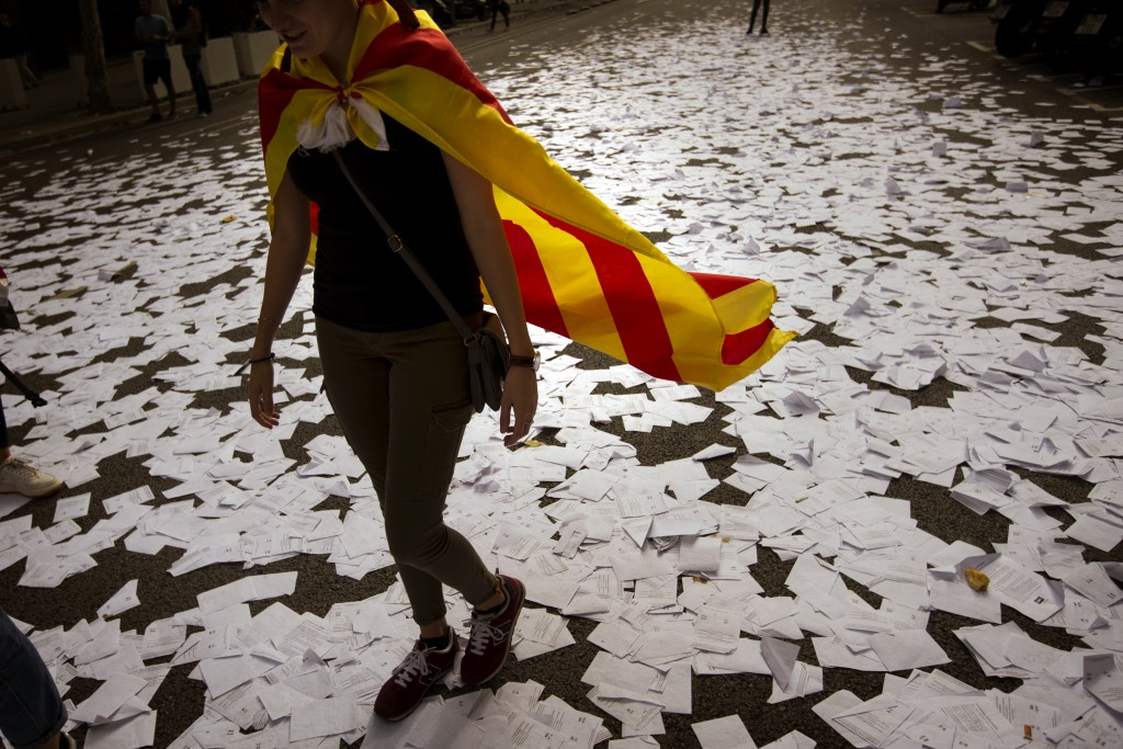 FILE - In this Tuesday Oct. 3, 2017 file photo a woman wearing an estelada or independence flag walks a long a street covered with referendum ballots ...