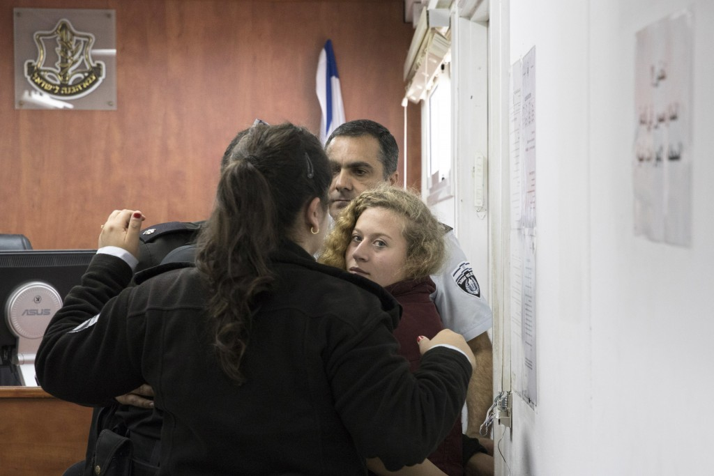 ISRAEL OUT - Palestinian Ahed Tamimi Is escorted at a military court near Jerusalem, Wednesday, Dec. 20, 2017. The 16-year-old girl who is seen in a v...