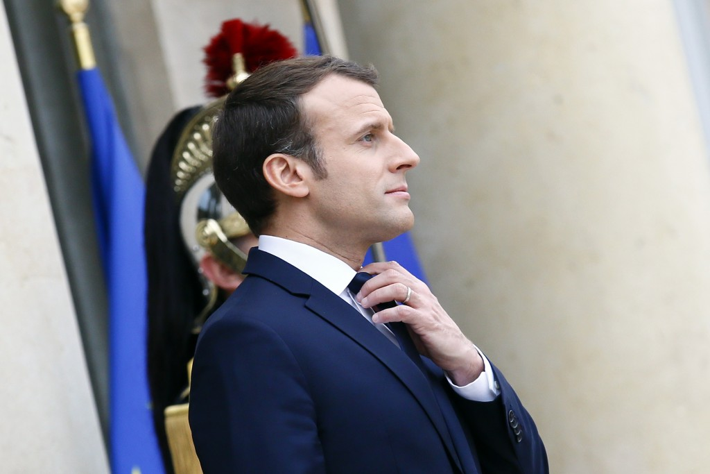 FILE - In this Dec.19, 2017 file photo, French President Emmanuel Macron adjusts his tie at the Elysee Palace, in Paris. As Macron turns 40 Thursday, ...
