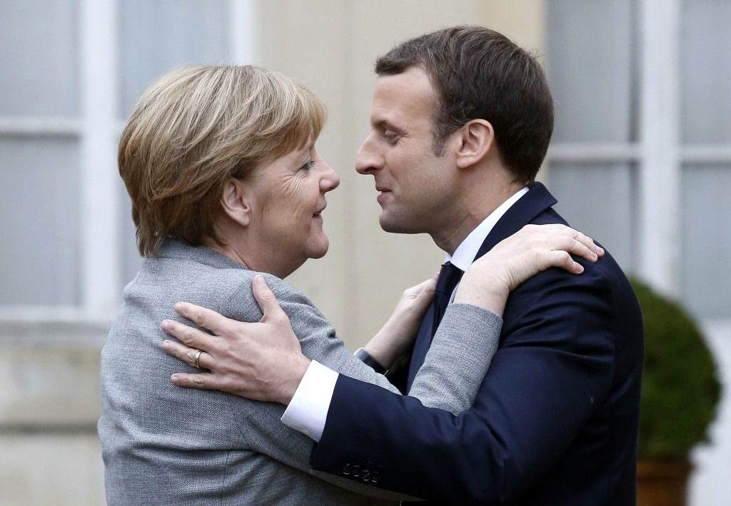 FILE - In this Dec.13, 2017 file photo, German Chancellor Angela Merkel, left, is welcomed by France's President Emmanuel Macron for conference to sup...