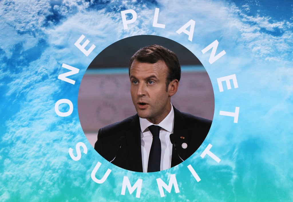 FILE - In this Dec.12 2017 file photo, French President Emmanuel Macron is pictured on a screen as he delivers a speech at the One Planet Summit, in B...